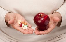 Senior Woman Holding Pills And Apple Royalty Free Stock Image