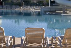 Chairs And Water Slide By Swimming Pool Stock Photography
