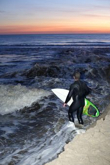 A Surfer Heads Out For A Sunset Sessions Stock Photo
