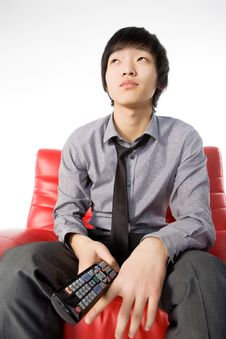 The Smiling Young Man In A Grey Shirt Watches TV Stock Photography