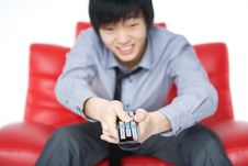 The Smiling Young Man In A Grey Shirt Watches TV Royalty Free Stock Image
