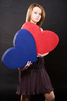 Pretty Girl In Dress Holding Two Hearts Stock Image