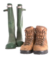 Old Walking Boots And Green Wellington Boots Royalty Free Stock Photography