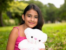 Girl In The Garden With Her Teddy Bear Stock Image