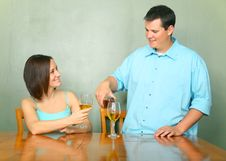 Young Couple Enjoying Wine On Kitchen Table Stock Photos
