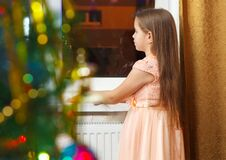 Free Little Girl Standing At The Window At Christmas Stock Photos - 78934883