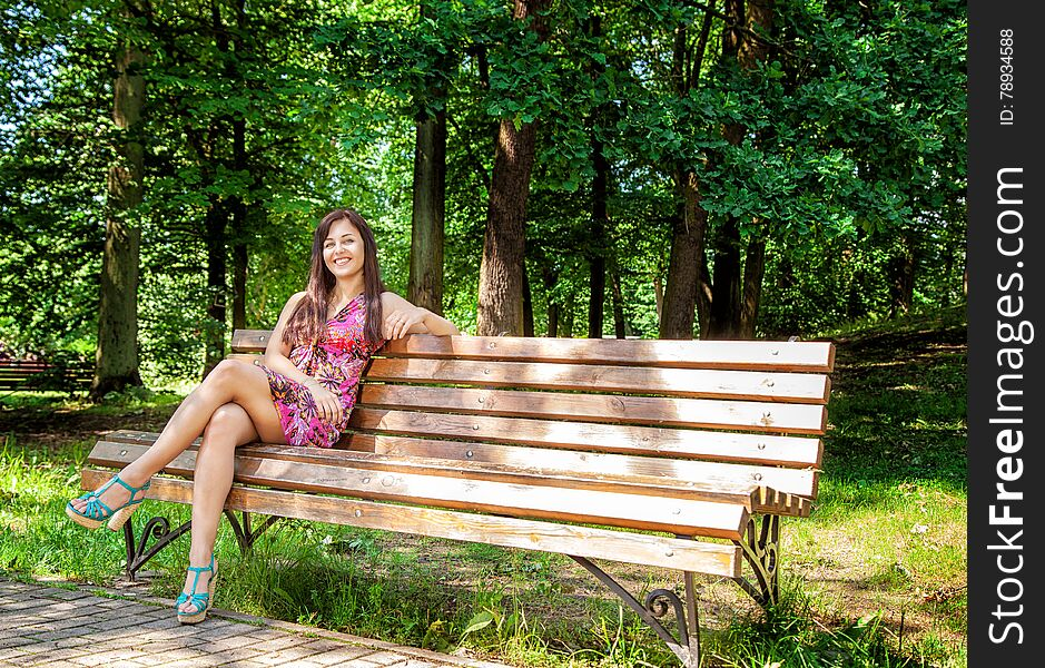 Young beautiful girl sitting on a park bench