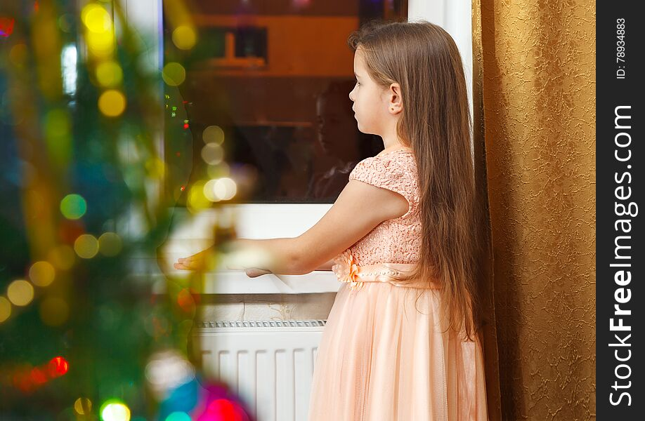 Little girl standing at the window at Christmas
