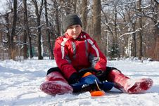 The Boy Sitting On A Sledge In Red Valenki. Stock Photos