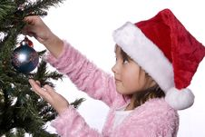 Free Girl Carefully Puts Ornament On Tree. Royalty Free Stock Photo - 7928965