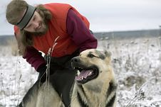 Smiling Bearded Man Playing With Alsatian Dog