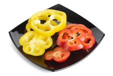 Slices Of Red And Yellow Pepper On A Black Plate Royalty Free Stock Image