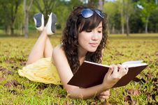 Girl Reading Book In The Outdoors Stock Images