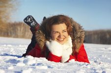 Attractive Girl Lays On White Snow And Smiles Stock Photos