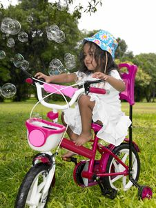 Free Girl In The Garden Riding Her Cycle Stock Photos - 7973633