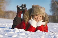 Attractive Girl Lays On Snow And Smiles Stock Images