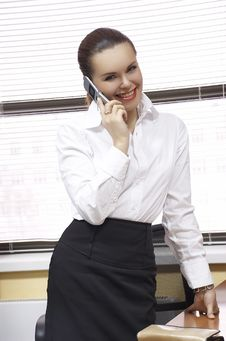 Woman At Office  Talks On The Phone Royalty Free Stock Photo