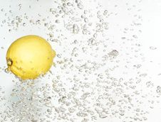 Lemon Is Dropped Into Clean Water. Royalty Free Stock Photos