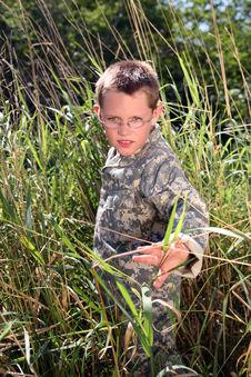 Young Boy In Camoflauge Hiding In The Grass Stock Photo