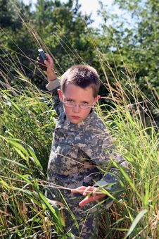 Free Boy In Camoflauge Raising Arm To Throw Grenade Stock Photo - 8020020