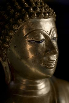 Gold Buddha In A Dimly Lit Room. Royalty Free Stock Photography