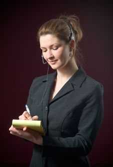 Free Beautiful Secretary Wearing Headset Taking Notes Stock Photography - 8075812