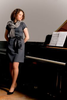 Free Pretty Dark Haired Young Girl Standing Near Piano Stock Photos - 8107813