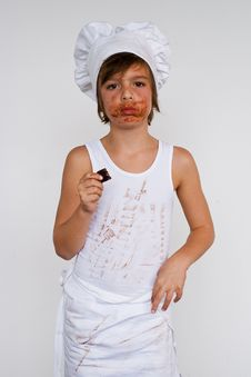 Free Young Baker Boy Eating Chocolate Stock Images - 8122894