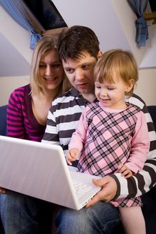 Little Girl With Parents Play With A Laptop Royalty Free Stock Image