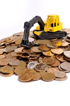 Yellow Excavator On A Big Heap Of Coins Royalty Free Stock Image