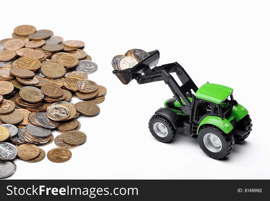 Green tractor raking up coins