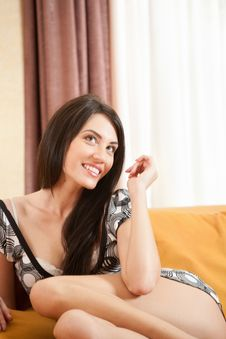Free Attractive Smiling Sexy Girl Sitting On Sofa Stock Image - 8173371