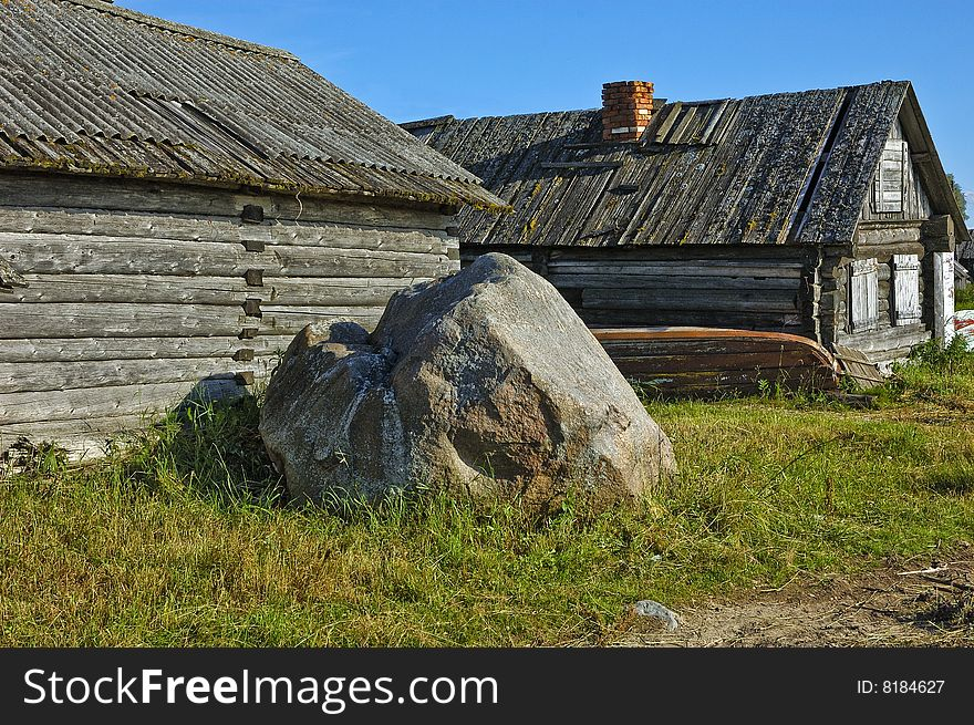 Old wooden shed and big stone