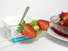 Cottage Cheese In Its Plastic Container With Fruits Skewer Stock Image