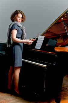 Free Young Girl Standing Near Piano Stock Image - 8202021