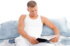 Reading Book - Male Reading In Bed Relaxing Stock Image