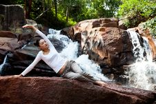 Young Woman Relaxing By The Waterfall Stock Image