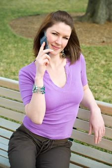 Pretty Girl On Park Bench Talking Cell Phone Stock Image