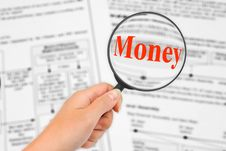 Magnifying Glass In Hand And Word Money Stock Photo