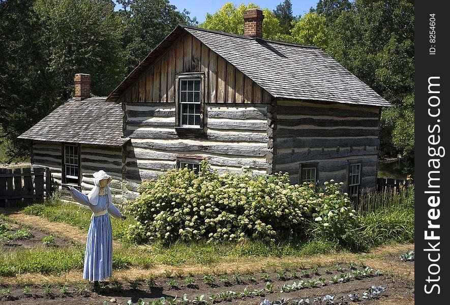 Scarecrow in Farm Garden and Log Cabin