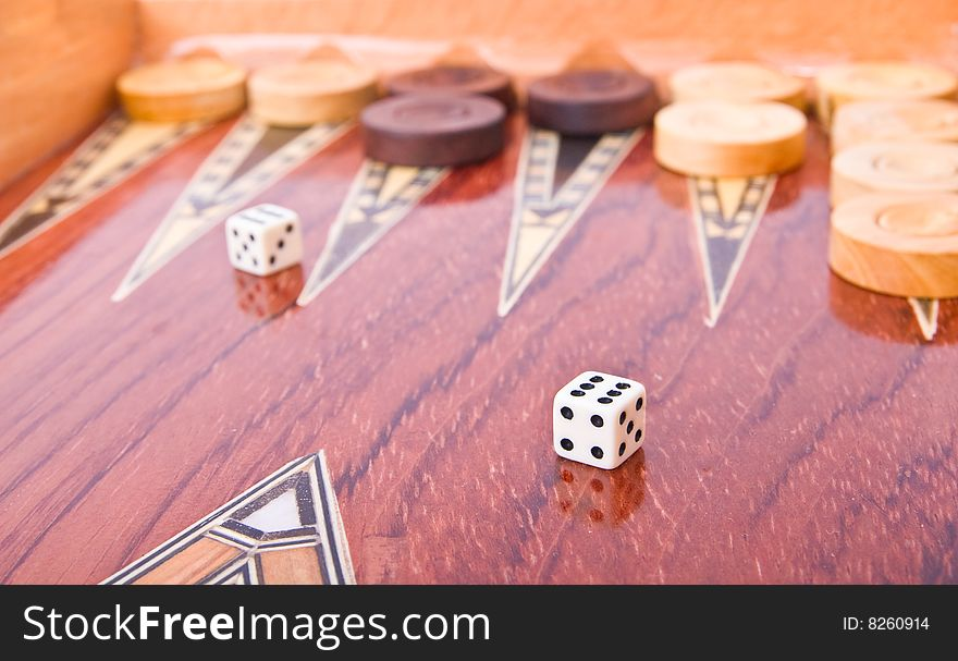 Ivory dices on wooden handmade backgammon board