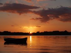 Dinghy Silhouetted In Sunrise Over The Bay. Stock Image