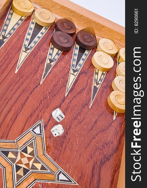 White dices falling on wooden backgammon board