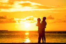 Free Couple Standing In The Seashore Hugging Each Other During Sunset Stock Photography - 82934102