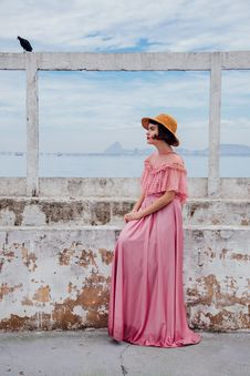 Free Woman In Pink Cold Shoulder Long Dress Sitting On Grey Concrete Bench Under Black Bird Royalty Free Stock Photography - 82934437