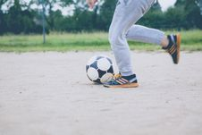 Free Person Kicking Soccer Ball On Gray Sand Stock Image - 82935351