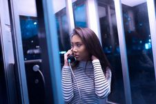 Free Woman In White And Black Stripe Long Sleeve Shirt Using Telephone Inside Telephone Booth During Night Time Stock Photography - 82936662