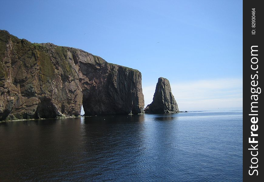 Grey Cliff on Blue Calm Sea during Daytime