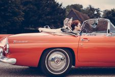 Free Couple Riding Red Ford Thunderbird During Daytime Royalty Free Stock Image - 82945556