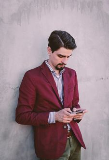 Free Man Wearing Maroon Blazer Leaning On Gray Concrete Wall While Using His Smartphone Stock Photography - 82946182